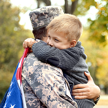 boy hugging his dad in uniform